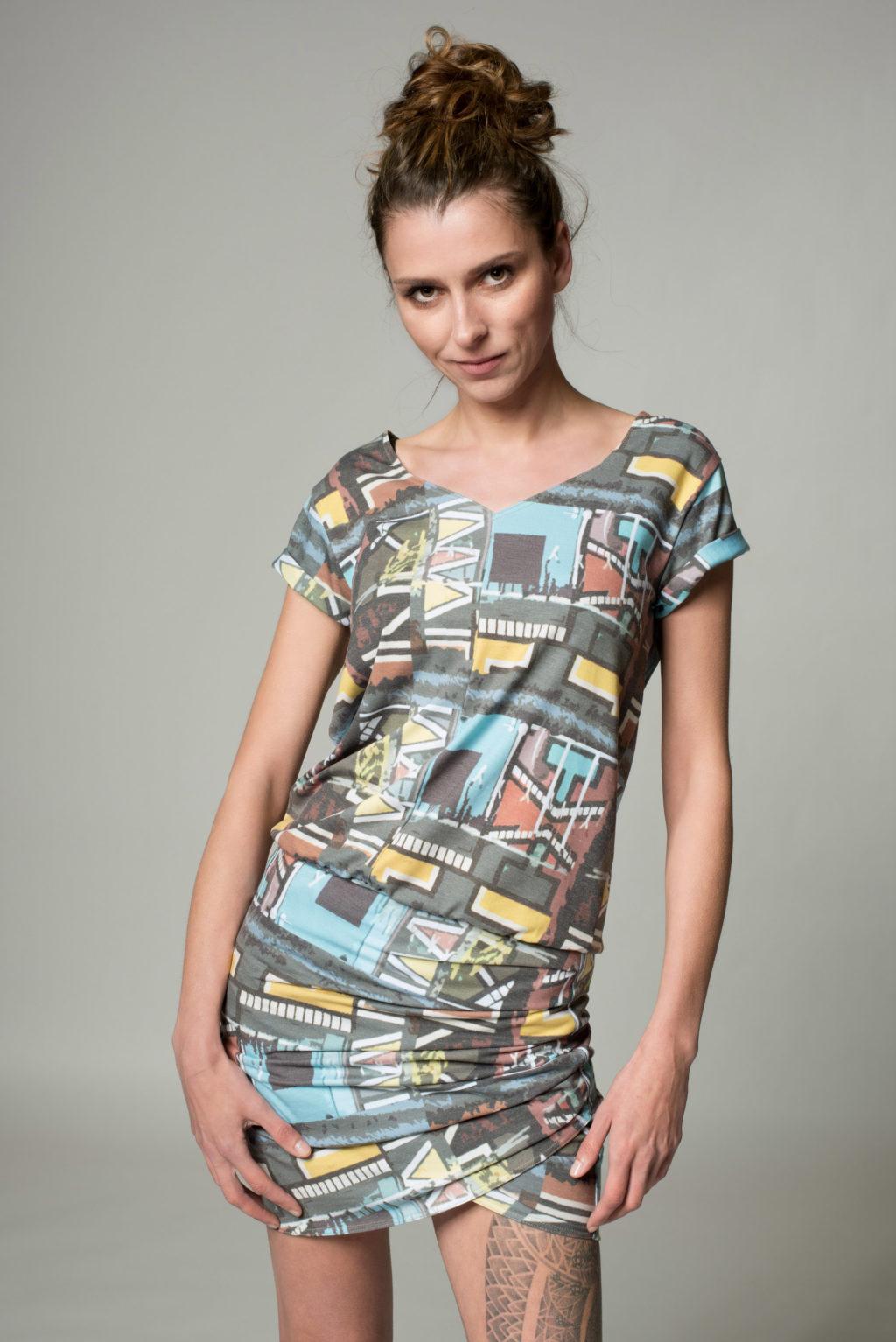 Frontansicht des drapierten Kleides Vibes mit geometrischen Mustern bedruckt un dmit V-Ausschnitt und Krempelärmeln. Kleid endet über dem Knie.