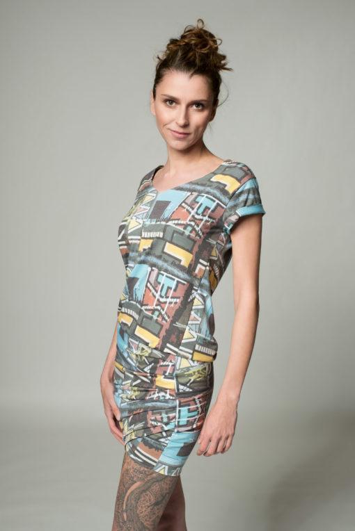 Seitenansicht des drapierten Kleides Vibes mit geometrischen Mustern bedruckt un dmit V-Ausschnitt und Krempelärmeln. Kleid endet über dem Knie.